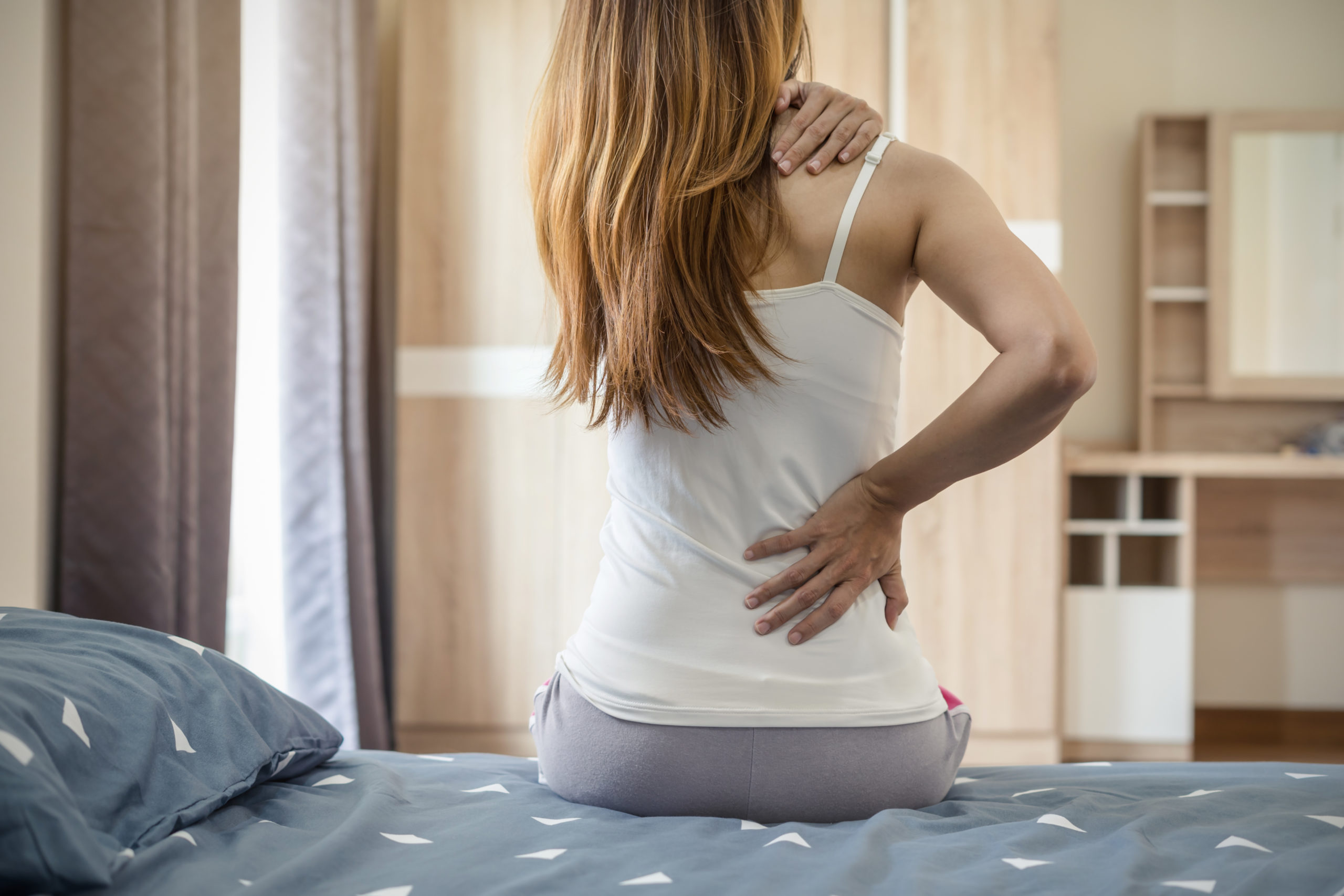Woman suffering from back ache on the bed, healthcare and problem concept
